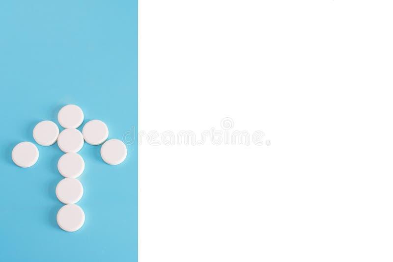 Witte die pillen op een blauwe pastelkleurachtergrond worden gemorst Pijlwijzer van pillen wordt gemaakt die Drugs en pillen stock fotografie