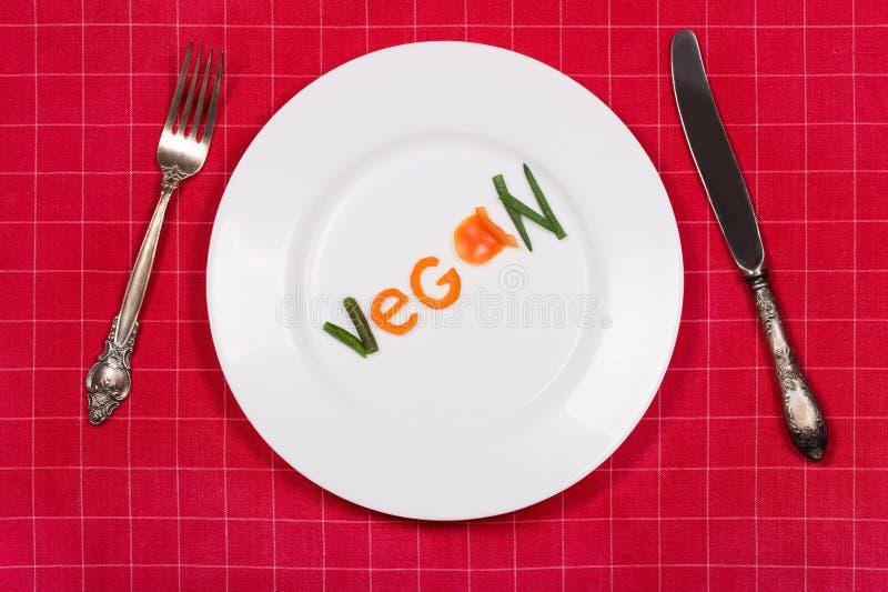 Witte die plaat met woordveganist van stukken groenten op rood wordt gemaakt stock afbeeldingen
