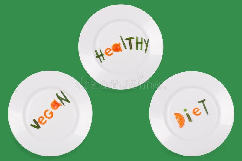 Witte die platen met gezonde woordenveganist, dieet van stukken groenten op groene achtergrond wordt gemaakt Reeks van drie beeld royalty-vrije stock foto's