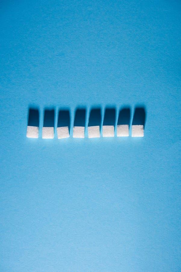 Witte die suikerkubussen in horizontale lijn op blauwe achtergrond worden geschikt Geïsoleerde De ruimte van het exemplaar stock fotografie