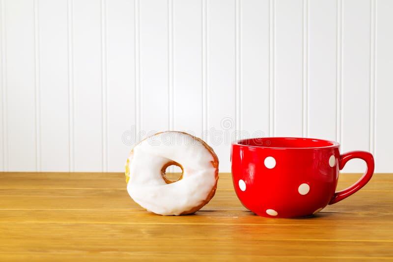 Witte doughnut met een rode mok op houten stock fotografie