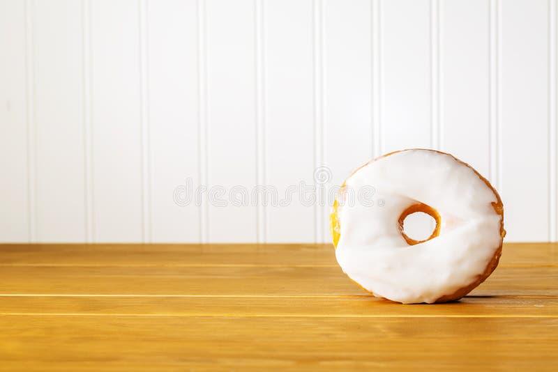Witte doughnut op een houten lijst stock afbeelding