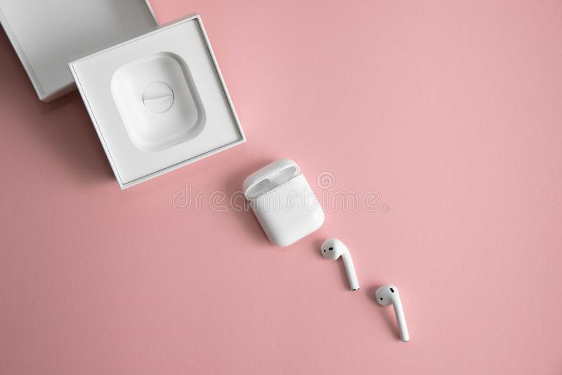 Witte draadloze hoofdtelefoons naast de lader en een witte, open doos van hen, diagonaal liggend op een roze achtergrond royalty-vrije stock foto