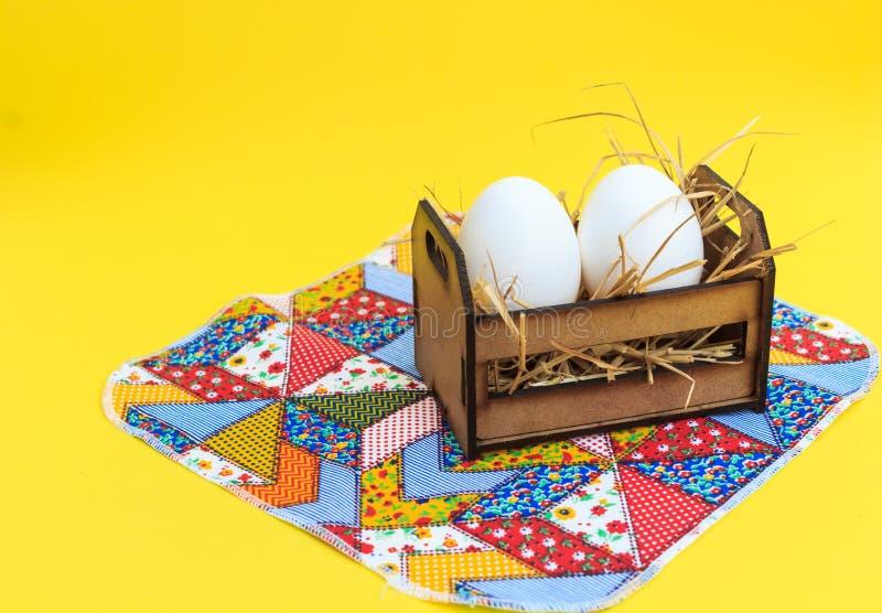 Witte eieren in een houten krat, op een lapwerkdeken, met gele achtergrond stock afbeelding