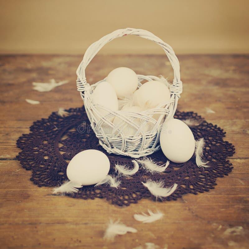Witte eieren in mand met retro Pasen-decoratie stock afbeelding