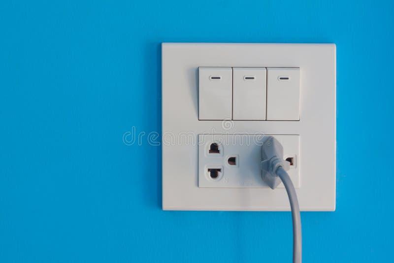 Witte elektrische afzet en schakelaar opgezet op blauwe muur stock afbeeldingen