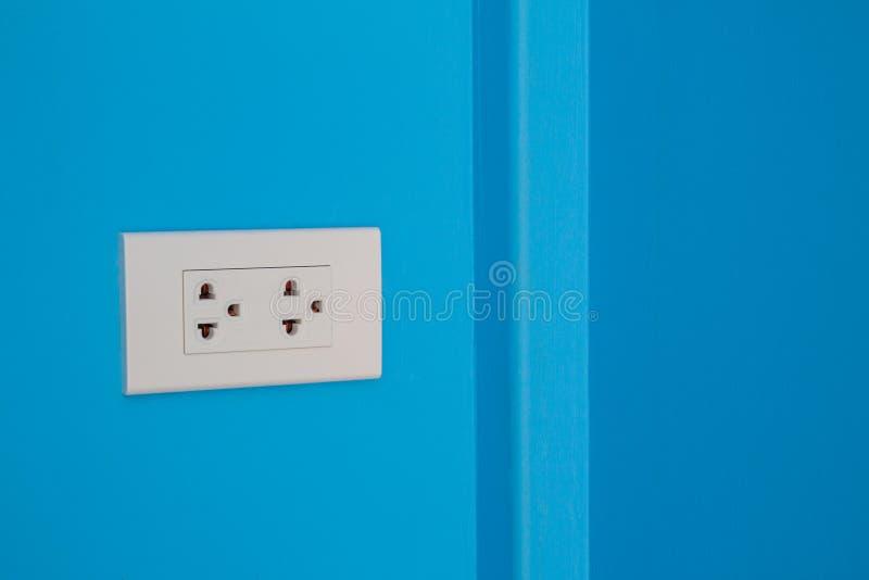 Witte elektrische afzet opgezet op blauwe muur stock afbeelding