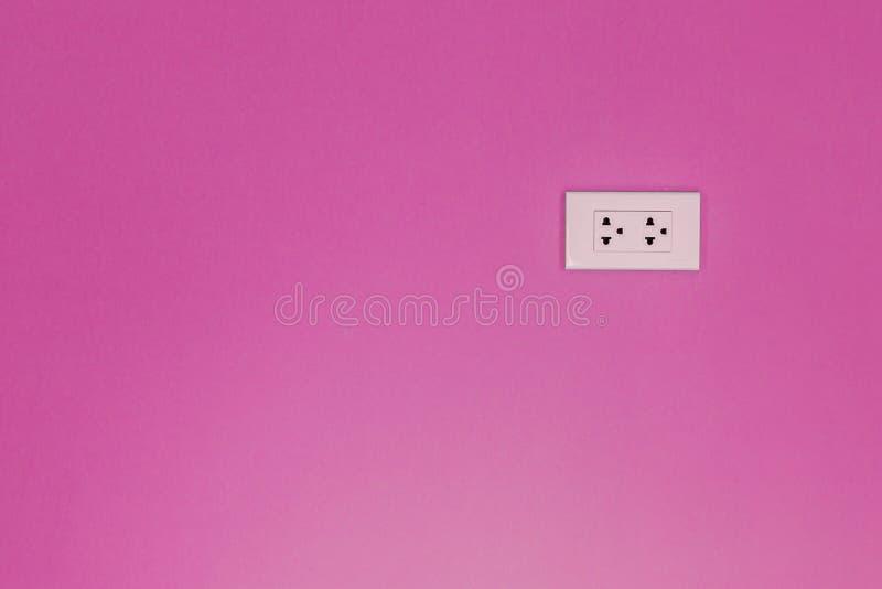 Witte elektrische afzet opgezet op roze muur stock fotografie