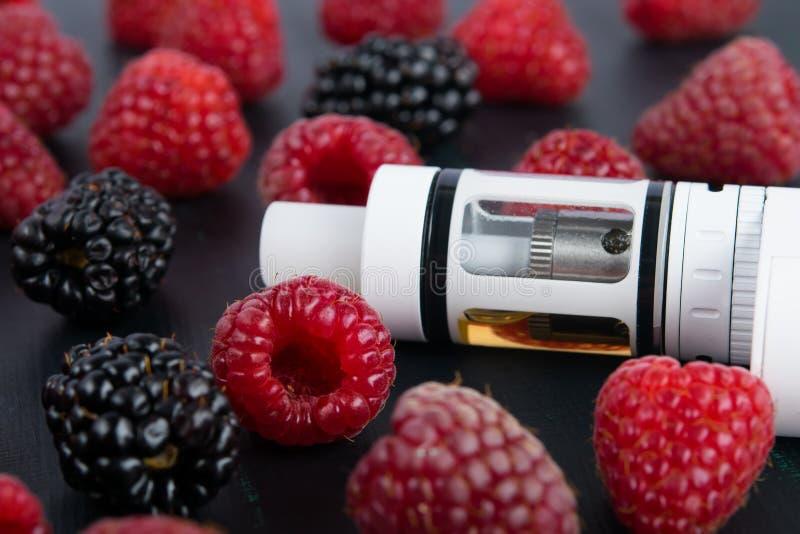Witte elektronische sigaret op een donkere lijst, met geassorteerde tuinbessen stock foto