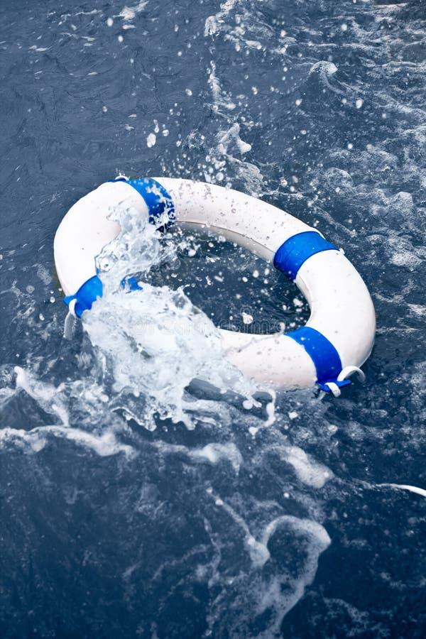 Witte en blauwe lifebelt, reddingsboei in oceaanonweersgolf stock fotografie