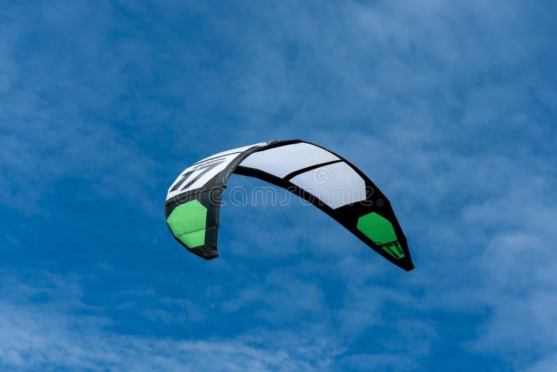 Witte en groene kitesurfing slepende vlieger in de lucht stock fotografie