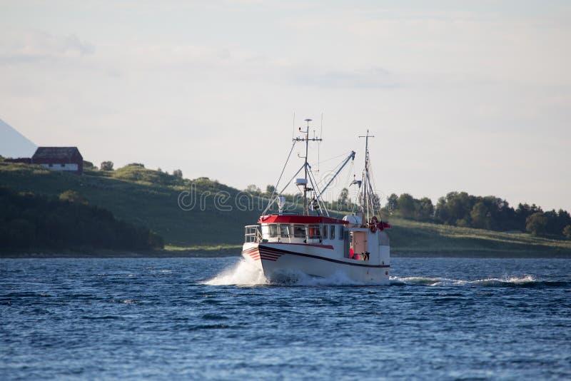Witte en rode vissersboot op het overzees Fjord in Noorwegen royalty-vrije stock afbeeldingen