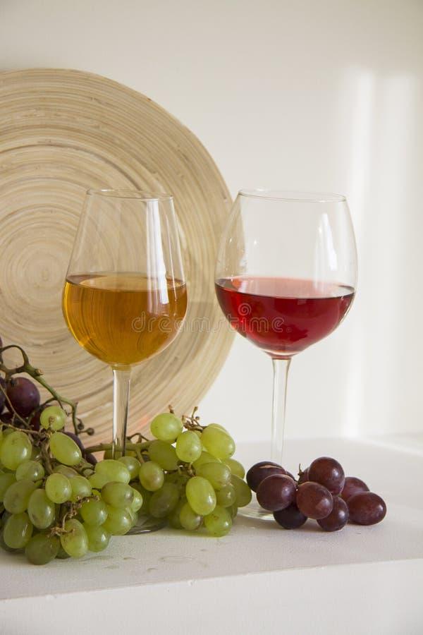 Witte en rode wijn met rode druivenverticaal stock foto's