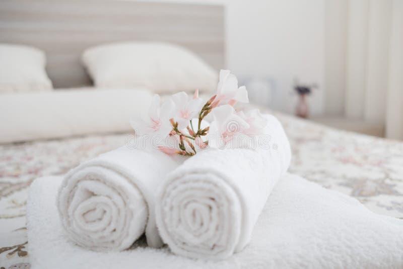 Witte en verse witgewassen pluizige handdoeken met bloem op bed in ho stock afbeelding