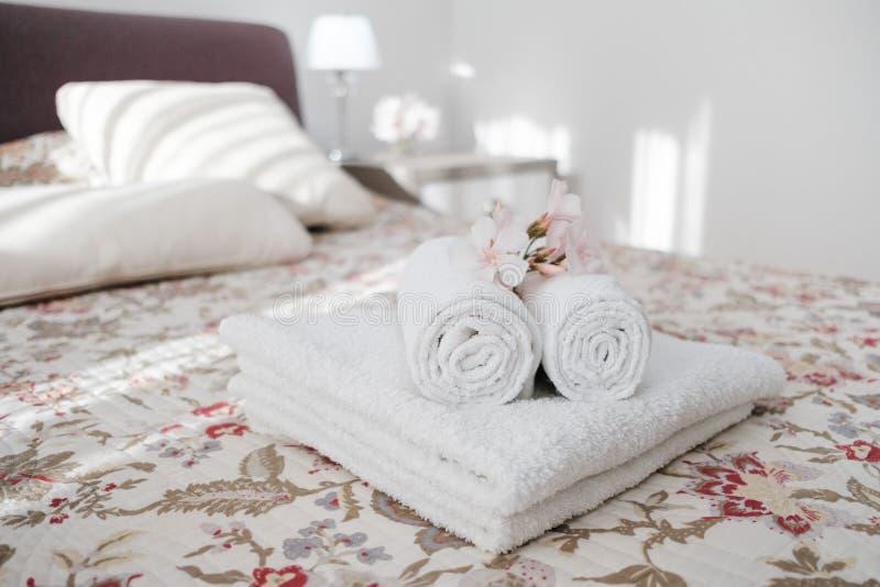 Witte en verse witgewassen pluizige handdoeken met bloem op bed in ho royalty-vrije stock afbeeldingen
