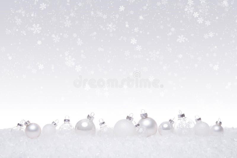 Witte en zilveren die Kerstmisballen op een rij op sneeuw worden geïsoleerd royalty-vrije stock fotografie