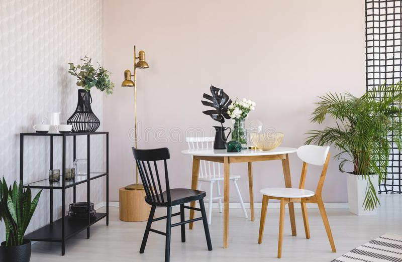 Witte en zwarte stoel bij houten lijst met installatie in eetkamerbinnenland met gouden lamp Echte foto stock illustratie