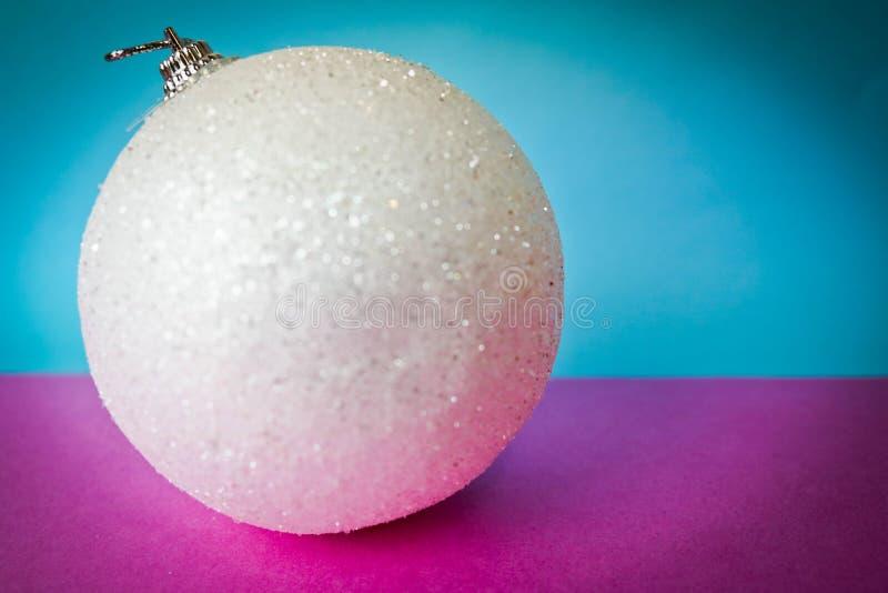 Witte feestelijke die Kerstmisbal van sneeuw kleine ronde Kerstmis, Kerstmisstuk speelgoed over fonkelingen op een roze purpere b stock afbeeldingen