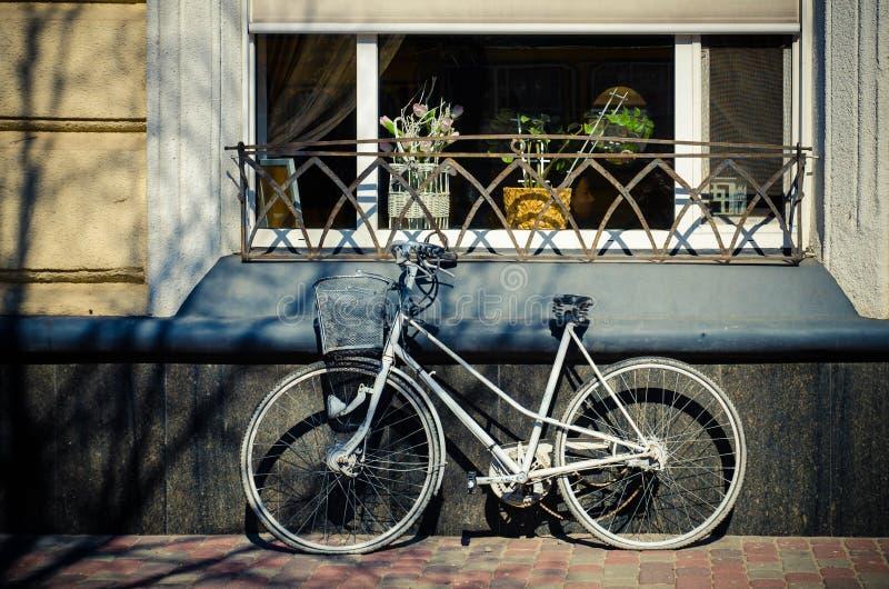 Witte fiets tegen de muur stock foto's