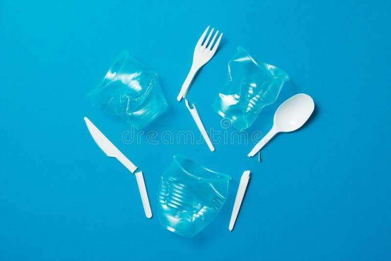 Witte gebroken plastic messen voor ??nmalig gebruik, lepels, vorken en plastic drankstro op een blauwe achtergrond Zeg nr aan pla royalty-vrije stock foto
