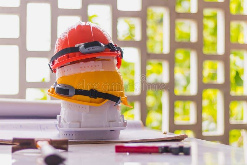 Witte, gele en oranje harde veiligheid, helmhoed voor veiligheidsproject van werkman of ingenieur op bureau en bouwplannen met  stock foto
