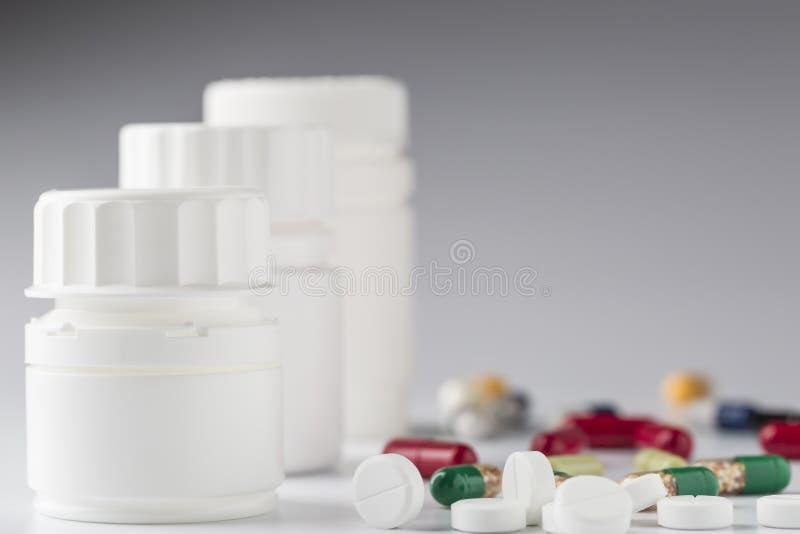 Witte geneeskundefles en diverse kleurrijke pillen stock afbeeldingen