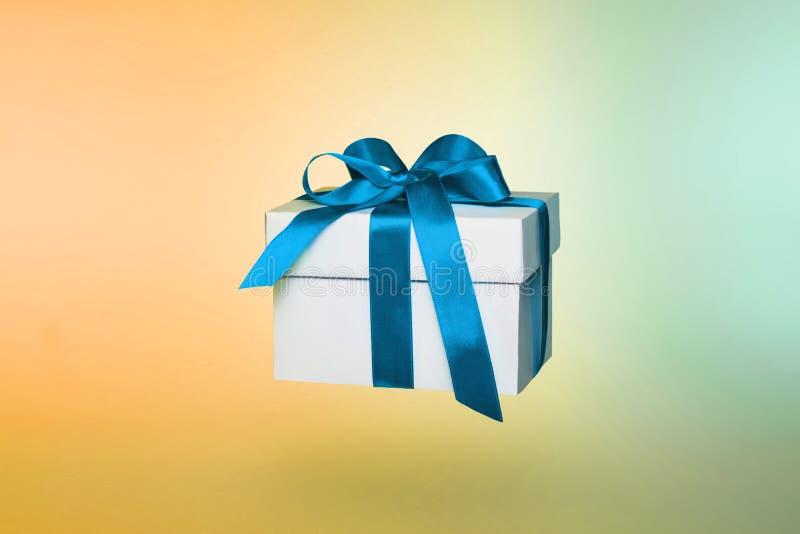 Witte giftdoos met blauw lint op gekleurde achtergrond royalty-vrije stock foto's