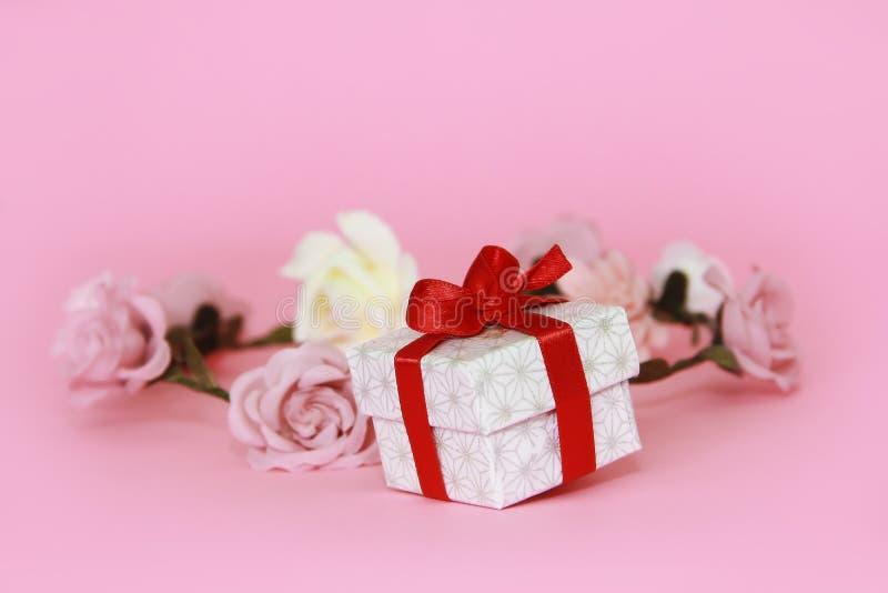 Witte giftdoos met een rode boog op een roze achtergrond met bloemen stock foto's