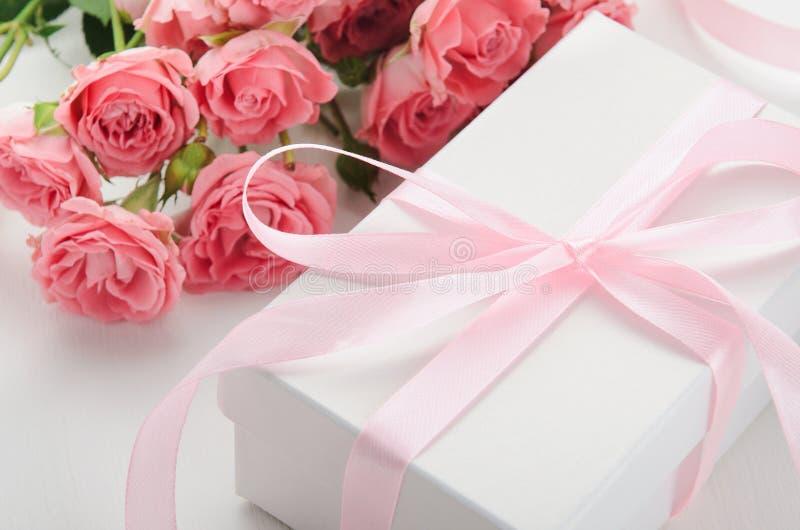 Witte giftdoos met een roze lint en een boeket van rozen op een witte achtergrond Een gift voor de Dag van Valentine, verjaardag stock foto's
