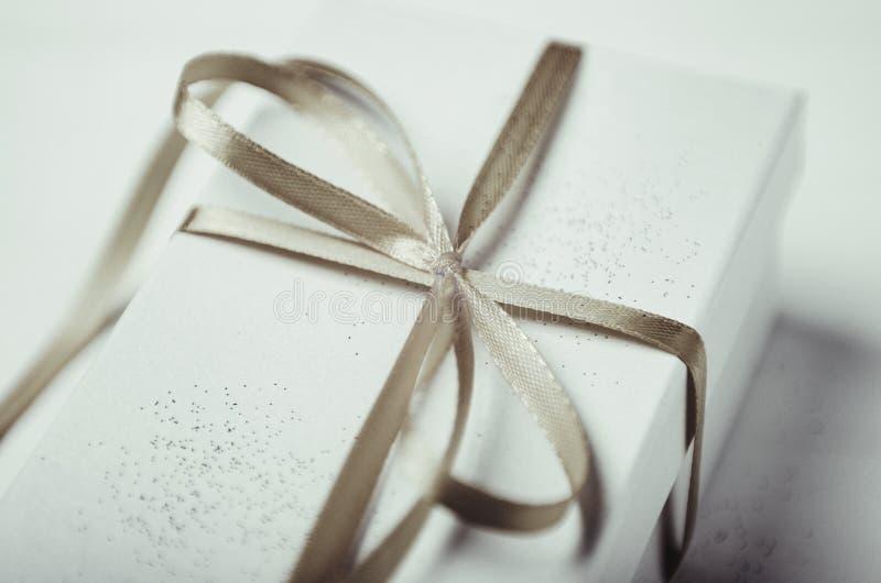 Witte giftdoos met fonkelingen en grijze boog op een witte achtergrond stock foto