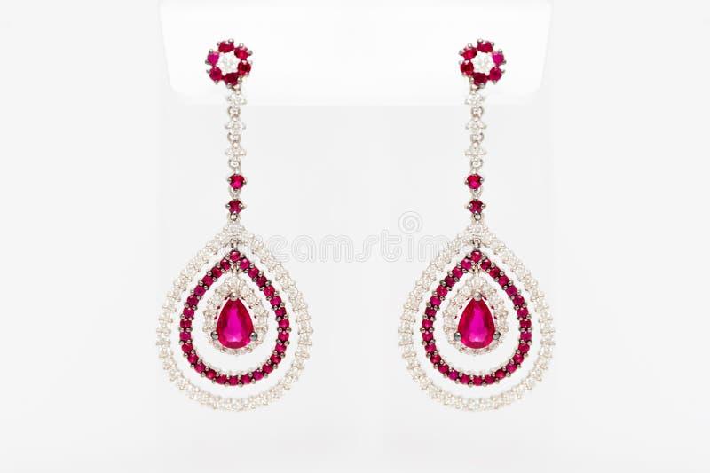 Witte gouden oorringen met diamanten en rode kostbare gemmen op lichte achtergrond Lange gouden oorringen Manierluxe stock foto's