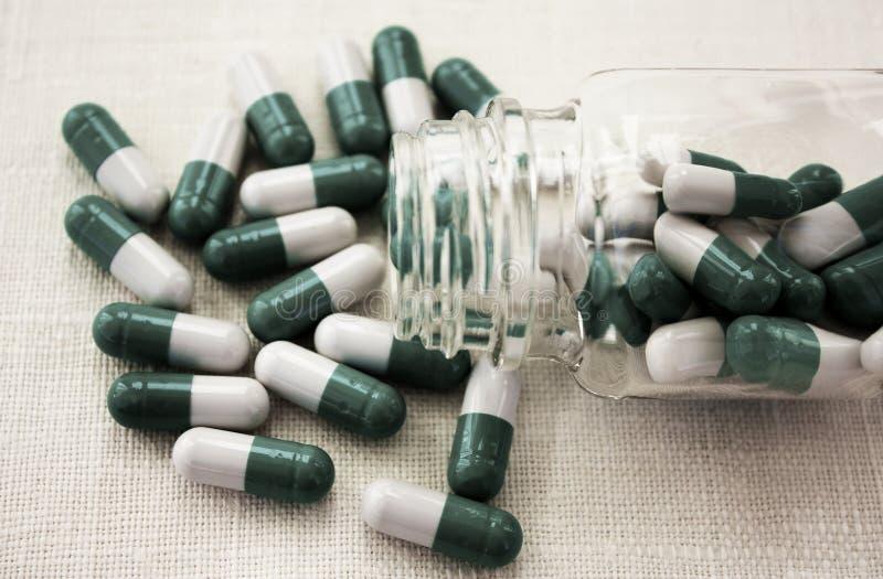 Witte groene capsules die uit transparante geneeskundefles, pillen en flesje morsen die op witte achtergrond liggen stock afbeeldingen