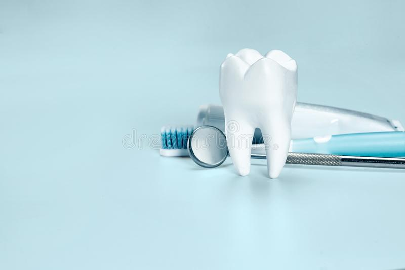 Witte grote gezonde tand, tandenborstel en tandpasta voor tandzorg, op lichtblauwe tandachtergrond royalty-vrije stock foto's