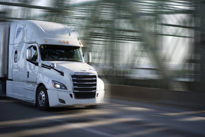 Witte grote installatie semi vrachtwagen met chroomtraliewerk die goederen i vervoeren stock foto's
