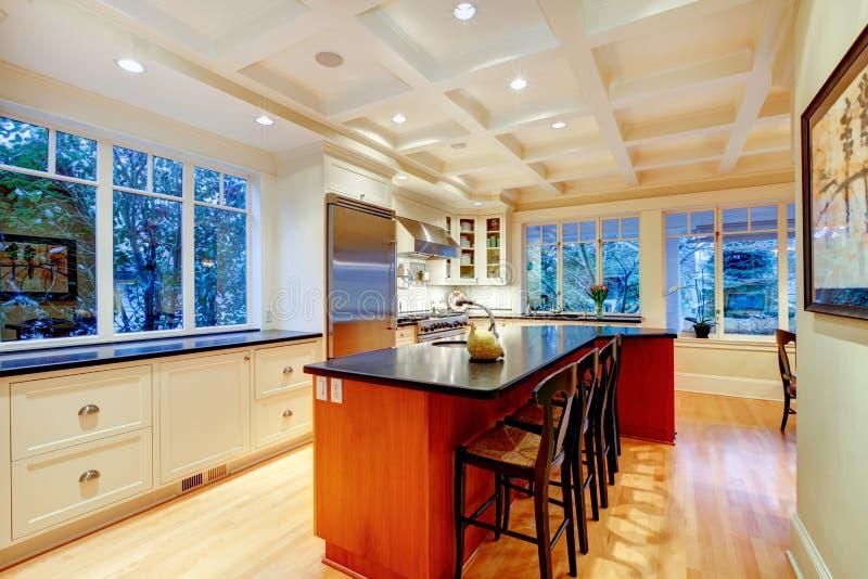 Witte grote luxekeuken met reusachtige houten eiland en ijskast. royalty-vrije stock afbeelding