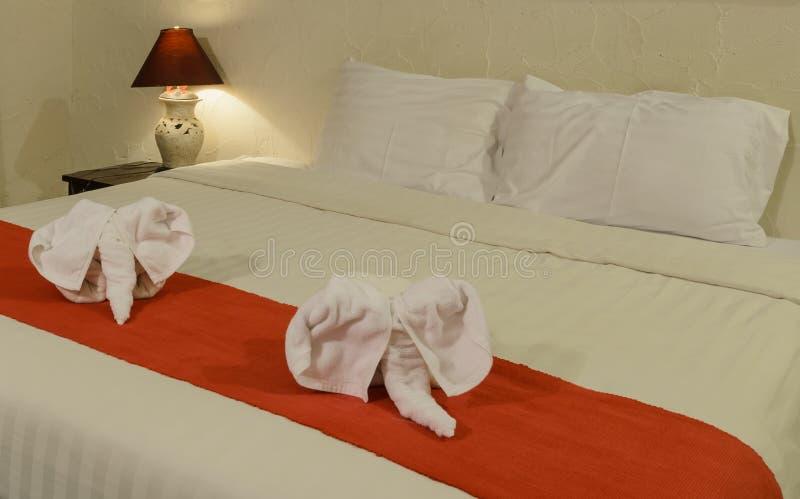 Witte handdoek in vorm van olifant op bed stock foto's
