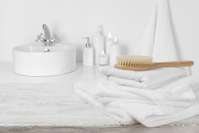 Witte handdoeken op houten lijst over vage eenvoudige badkamersachtergrond stock fotografie