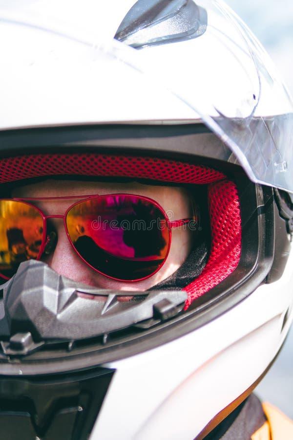 Witte helm en rode zonnebril Fietsermeisje die een motorfietsuitrusting, beschermende kleding, materiaal, close-upportret dragen stock foto