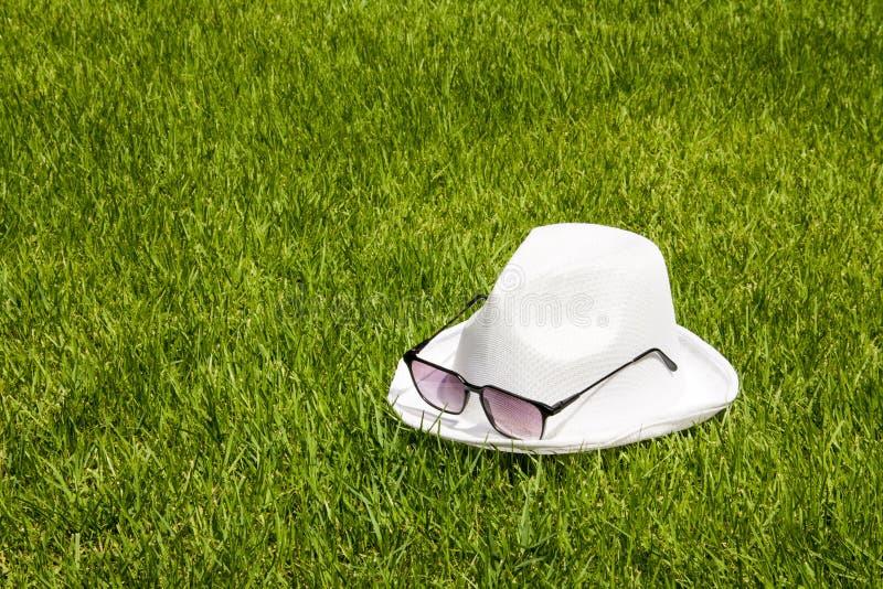 Witte hoed en zonnebril op de groene grasachtergrond royalty-vrije stock afbeelding