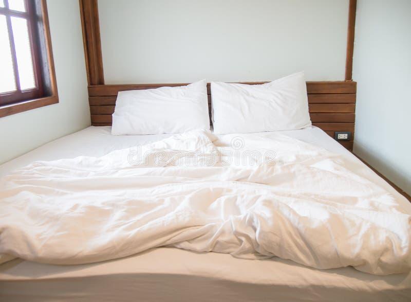 Witte hoofdkussens op het bed en een slordige deken in de slaapkamer royalty-vrije stock afbeelding
