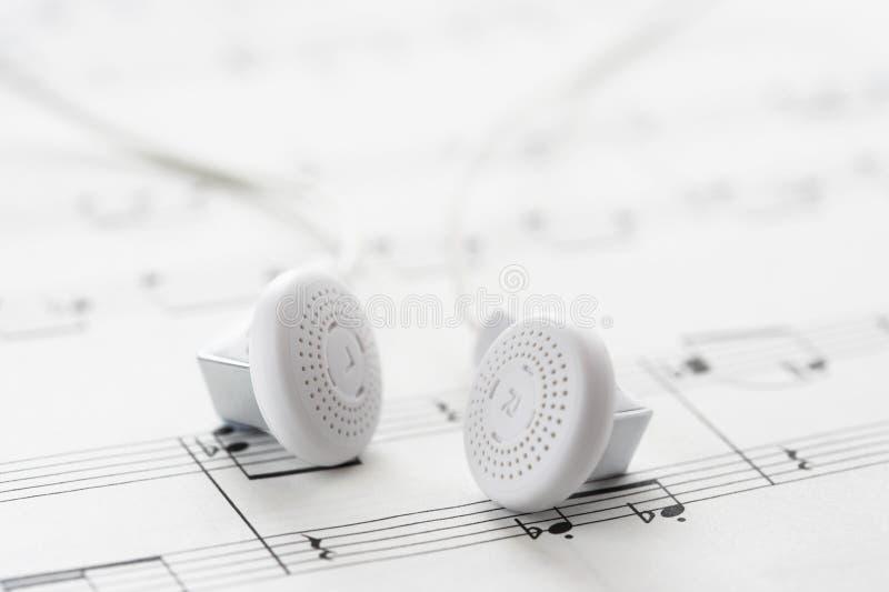 Witte hoofdtelefoons op bladmuziek royalty-vrije stock foto's