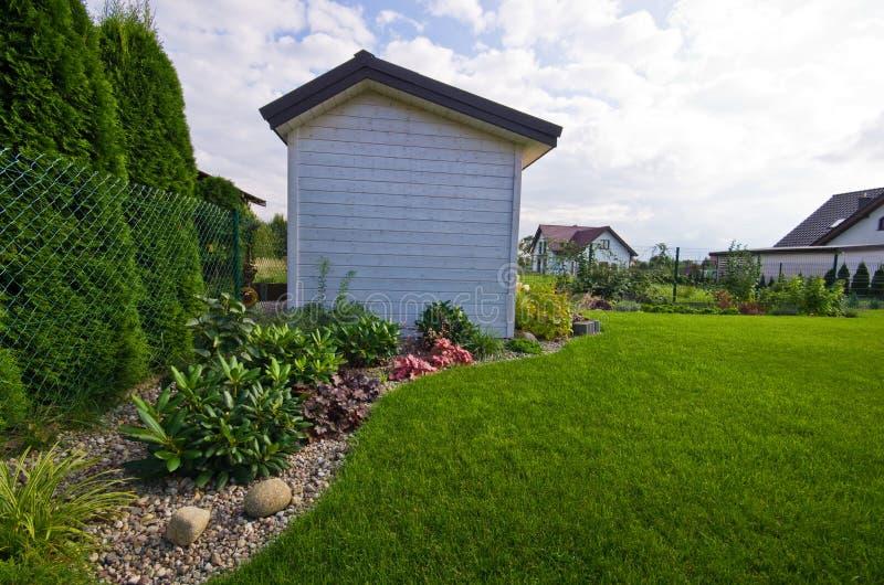 Witte houten afgeworpen tuin of hut met bloemen en installaties stock afbeeldingen