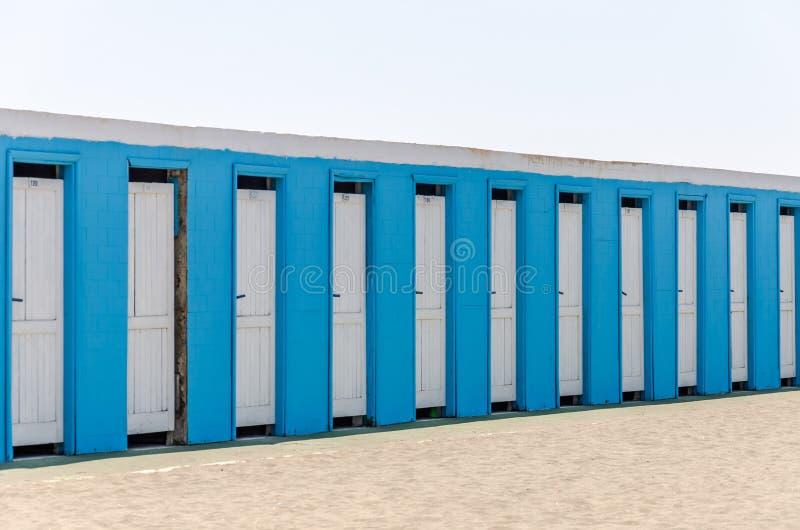 Witte houten deuren in een blauw gebouw voor veranderende kleren op het strand stock foto