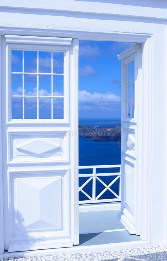 Witte houten lichte open deur Achter de deur is een mooie turkooise overzees en bergen royalty-vrije stock fotografie