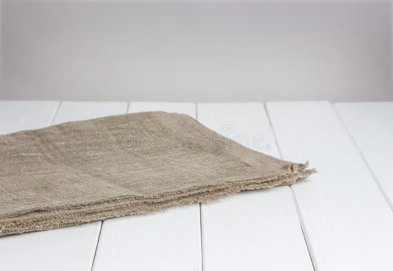 Witte houten lijst met tafelkleed, lichte achtergrond voor productmontering stock foto