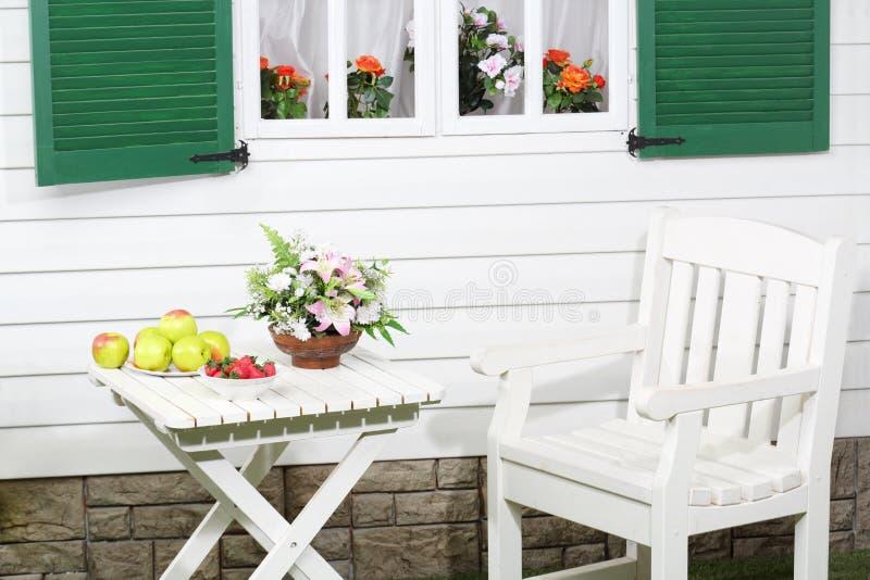 Witte houten lijst met vruchten en bloemen en stoel royalty-vrije stock afbeeldingen