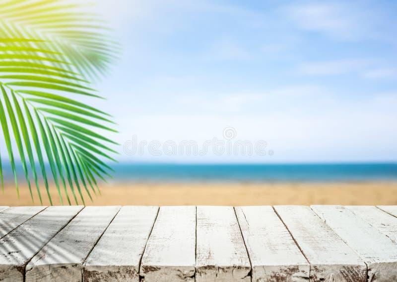 Witte houten lijstbovenkant met onduidelijk beeld overzees strand en kokosnotenblad De achtergrond van de vakantiezomer stock afbeelding