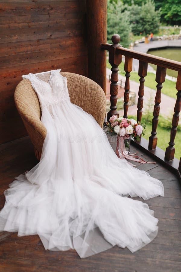 Witte huwelijkskleding die op leunstoel op houten balkon met mooi landschap liggen Bruid` s ochtend Het boeket van het huwelijk stock foto's