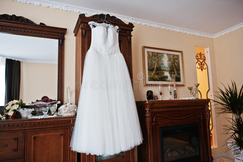Witte huwelijkskleding op hangers voor bruid bij ruimte stock foto's