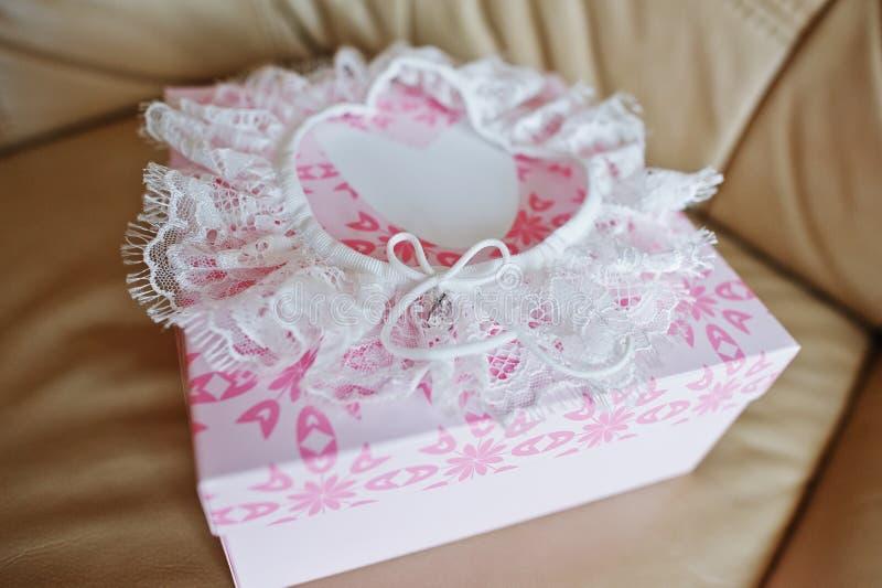 Witte huwelijkskouseband op roze doos bij leerbank stock fotografie